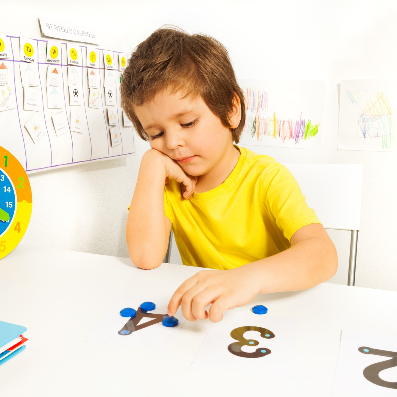 Boy puts blue coins as values on the numbers during math exercise as part of Applied Behavior Analysis (ABA) sitting at the table indoors